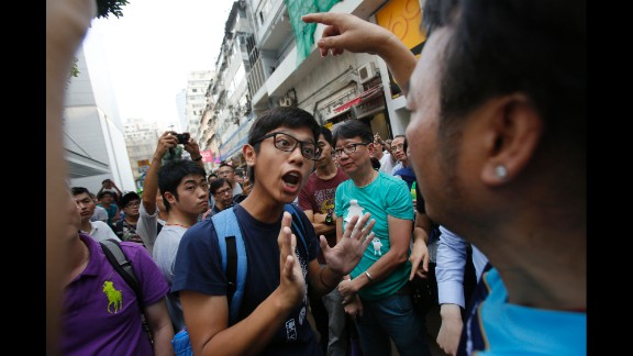 A protester tries to negotiate with angry residents trying to remove barricades blocking streets in Hong Kong