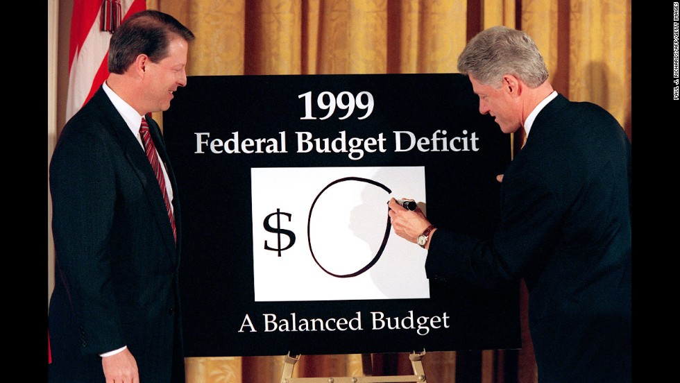 "Vice President Gore looks on as Clinton places an ""0"" on the board showing what the federal deficit will be after unveiling his balanced budget plan for 1999, during a ceremony at the White House on February 2, 1998. The President declared an end to ""an era of exploding deficits,"" sent a $1.73 trillion budget to Congress that promised the first surplus in more than three decades."