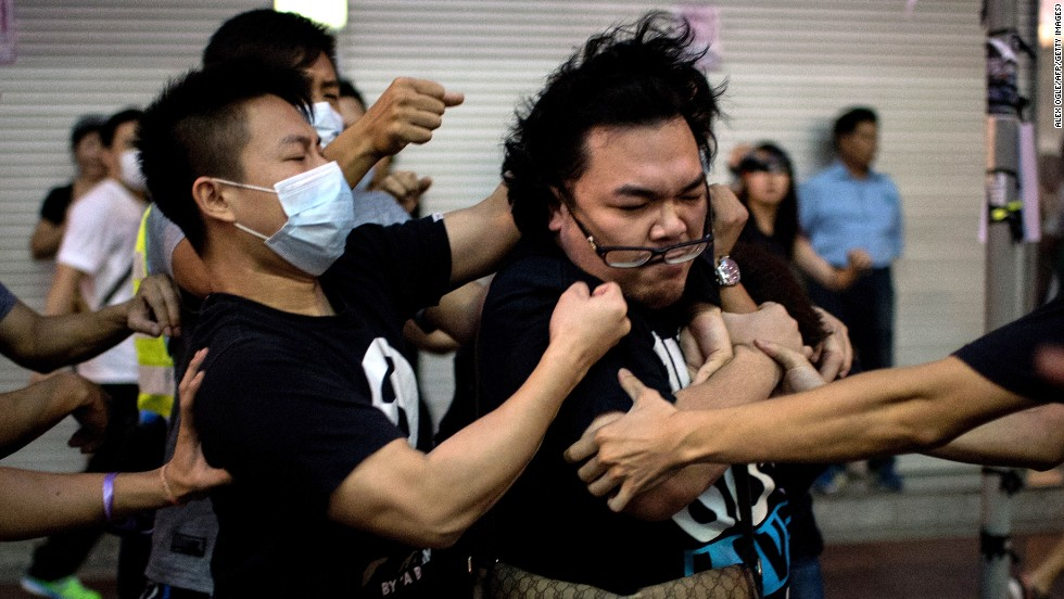 A group of men in masks fight with a man who tried to stop them from removing barricades from a pro-democracy protest area in the Causeway Bay district of Hong Kong on Friday, October 3.