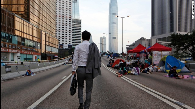 A man walks to work as pro-democracy demonstrators sleep on the road in the occupied areas surrounding the government complex in Hong Kong on Monday, October 6.