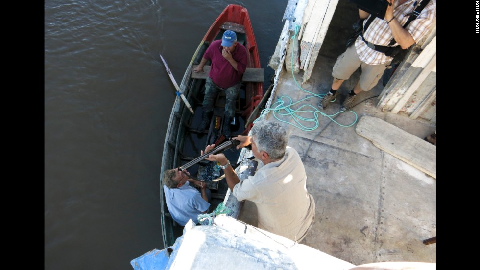 Bourdain speaks with a local fisherman who is selling shotguns along the Paraguay River.