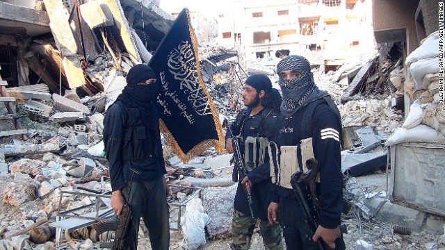 Fighters from the al-Qaeda group in the Levant, Al-Nusra Front, stand among destroyed buildings near the front line with Syrian government solders in Yarmuk Palestinian refugee camp, south of Damascus on September 22, 2014.