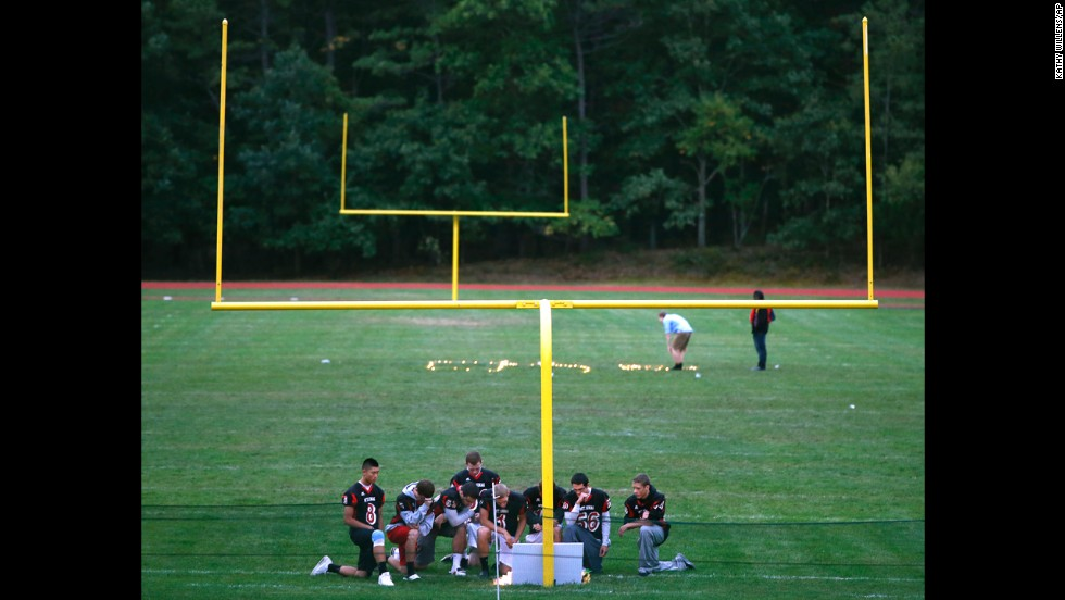 "Football players from Mount Sinai High School pause at a makeshift memorial Thursday, October 2, at Shoreham-Wading River High School in Shoreham, New York. It was one day after <a href=""http://www.cnn.com/2014/10/02/us/new-york-football-player-death/"">Tom Cutinella</a>, a 16-year-old student at Shoreham-Wading River, suffered a serious head injury during a football game and died at the hospital, according to Suffolk County Police spokeswoman Joan Jesinger."