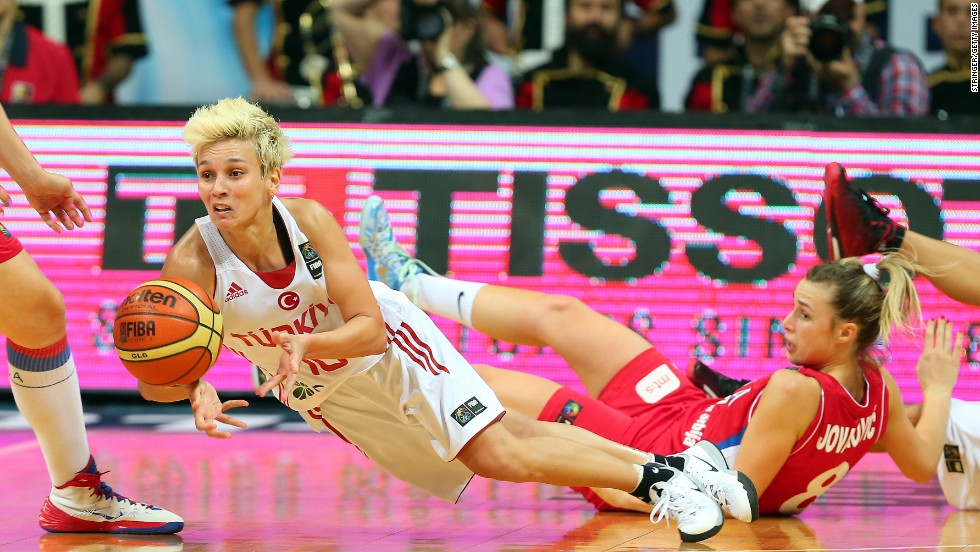 Turkey's Isil Alben, in white, falls to the floor Friday, October 3, while playing Serbia in the quarterfinals of the FIBA World Championship in Istanbul. Turkey won the game but lost in the semifinals to Spain. The United States defeated Spain in the final.