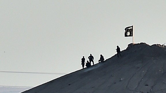 Caption:ALTERNATIVE CROP - BEST QUALITY AVAILABLE Alleged Islamic State (IS) militants stand next to an IS flag atop a hill in the Syrian town of Ain al-Arab, known as Kobane by the Kurds, as seen from the Turkish-Syrian border in the southeastern town of Suruc, Sanliurfa province, on October 6, 2014. Two flags of Islamic State (IS) jihadists seeking to take the Syrian town of Kobane were flying on the eastern side of the town, an AFP photographer reported. The flags, black with the Arabic lettering of the group, were seen by the photographer from the Turkish side of the border. One flew on a building while another larger flag was planted on a hill. AFP PHOTO / ARIS MESSINIS (Photo credit should read ARIS MESSINIS/AFP/Getty Images)
