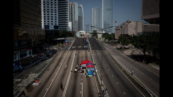 Protesters walk up an empty street inside the protest site near Hong Kong