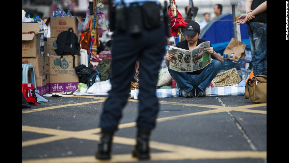 A pro-democracy protester reads a newspaper in Hong Kong's Mong Kok district on Tuesday, October 7, as a police officer stands nearby.