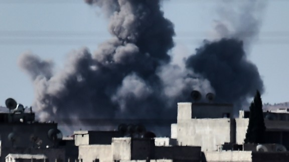 aption:Smoke rises from the southwest of the Syrian town of Ain al-Arab, known as Kobane by the Kurds, following air strikes as seen from the Turkish-Syrian border in the southeastern town of Suruc, Sanliurfa province, on October 7, 2014. Fresh air strikes by the US-led coalition hit positions held by Islamic State jihadists in the southwest of the key Syrian border town of Ain al-Arab (Kobane), according to an AFP journalist just across the border in Turkey. The strikes came a day after the extremists pushed into Kobane, seizing three districts in the city's east after fierce street battles with its Kurdish defenders. AFP PHOTO / ARIS MESSINIS (Photo credit should read ARIS MESSINIS/AFP/Getty Images)