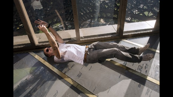 A visitor lies down to take a selfie on the new glass floor of Paris