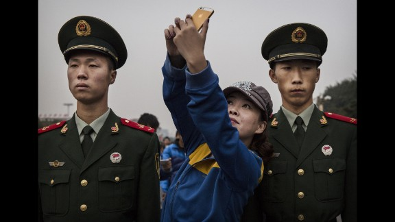 A woman poses for a selfie between two soldiers in Beijing on Wednesday, October 1. It was China