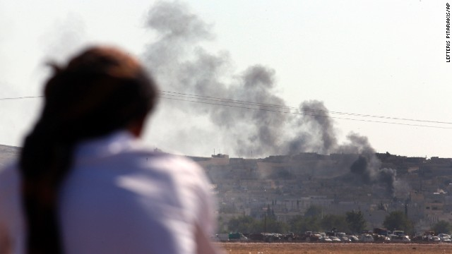 A Turkish Kurd sitting in the outskirts of Suruc, on the Turkey-Syria border, watches as smoke rises from a strike in Kobani, Syria, where the fighting between militants of the Islamic State group and Kurdish forces intensified, Tuesday, Oct. 7, 2014. Kobani, also known as Ayn Arab and its surrounding areas have been under attack since mid-September, with militants capturing dozens of nearby Kurdish villages. (AP Photo/Lefteris Pitarakis)
