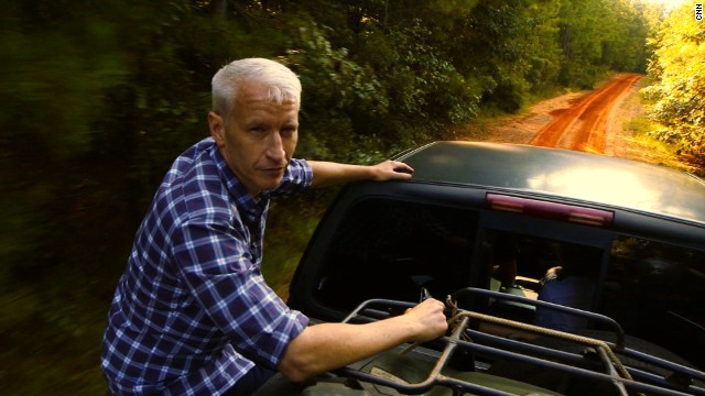 Anderson Cooper in the back of a pick-up truck, driving to an old Cooper family cemetery along the Mississippi-Alabama border.