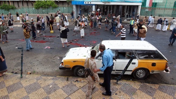 Yemeni security forces and Shiite Huthi militiamen stand next to pools of blood on the ground after a powerful suicide bombing rocked the Yemeni capital Sanaa on October 9, 2014.