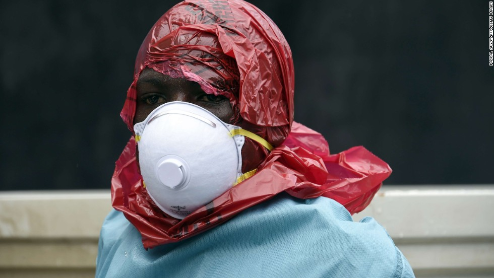Most people in Ebola-affected areas do not have access to protective suits. Red Cross volunteers have improvised their protective wear and cover their heads with red plastic bags. They cut a hole in the bag to see and breathe.<br />