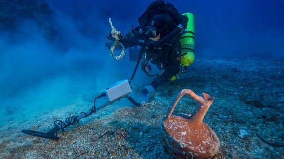 """After spending the last month at the historic wreck site, the Woods Hole Oceanographic Institute (WHOI) announced that an international team of archaeologists had recovered new items from the Antikythera wreck. Pictured, Greek technical diver Alexandros Sotiriou discovers an intact """"lagynos"""" ceramic table jug and a bronze rigging ring. The new items have indicated the wreck site is much bigger than previously believed, scattered across 300 meters of seafloor."""
