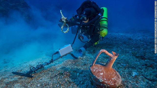 "Greek technical diver Alexandros Sotiriou discovers an intact ""lagynos"" ceramic table jug and a bronze rigging ring on the Antikythera shipwreck."