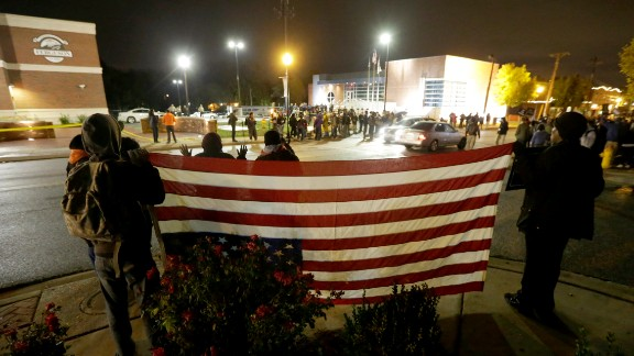 Protesters gather across the street from the Ferguson, Mo., police station holding an inverted American flag in a continuing protest of the shooting of Michael Brown, Friday, Oct. 10, 2014, in Ferguson, Mo. (AP Photo/Charles Rex Arbogast)