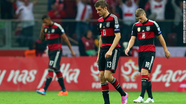 Thomas Muller (center) and Toni Kroos of Germany trudge off the pitch after being defeated by Poland in Warsaw.