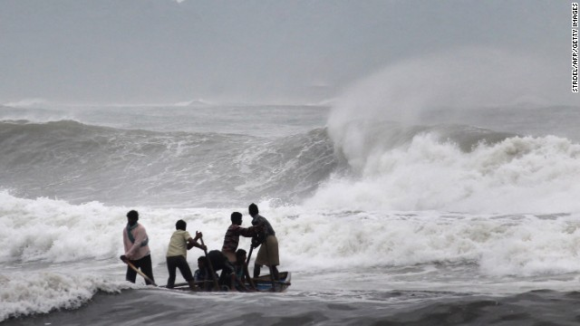 Indian fishermen negotiate rough waves ahead of Cyclone Hudhud's expected landfall.