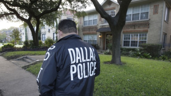 CORRECTS BYLINE - Police stand guard outside the apartment of a hospital worker, Sunday, Oct. 12, 2014, in Dallas. The Texas health care worker, who was in full protective gear when they provided hospital care for Ebola patient Thomas Eric Duncan, who later died, has tested positive for the virus and is in stable condition, health officials said Sunday. (AP Photo/LM Otero)