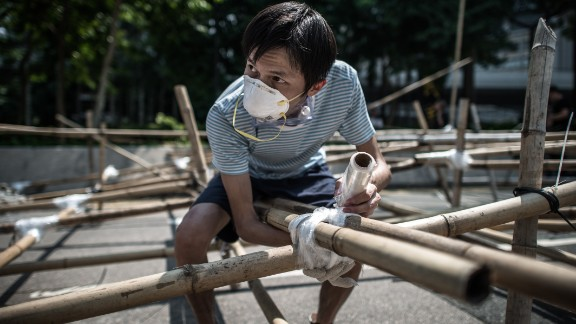 A demonstrator sets up a new barricade made of bamboo in Hong Kong on October 13.