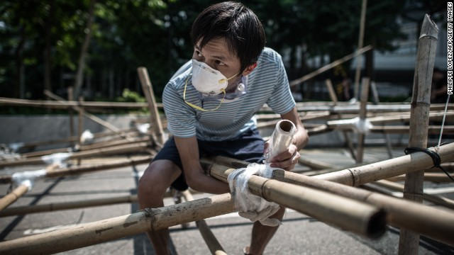 A pro-democracy demonstrator sets up a new barricade made of bamboo in Hong Kong on October 13.