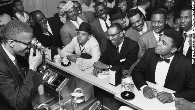 Malcolm X, left, takes a picture of a tuxedo-clad Ali surrounded by jubilant fans in March 1964.
