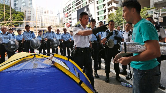 Police ask a protester to leave the main road of Hong Kong