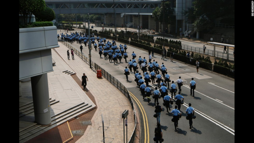 Police officers run to barricades set up by protesters on October 14.