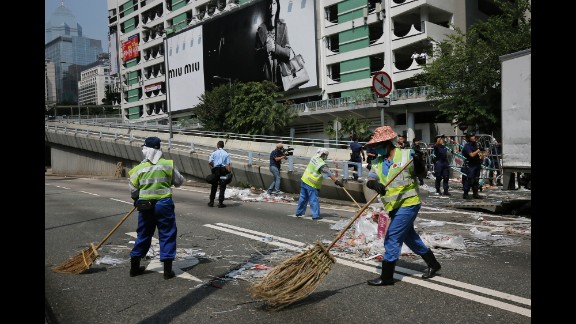 Cleaners sweep the main road after the police