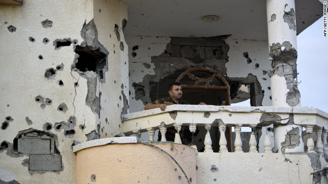 A Palestinian stands on a balcony destroyed in the 50-day conflict between Hamas militants and Israel, in Shejaiya neighbourhood in the east of Gaza city on October 12 ,2014.