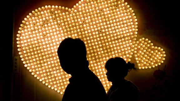 NANJING, CHINA - FEBRUARY 14: (CHINA OUT) A couple walk past hearts formed by 999 electric bulbs which were signed with people's autographs on Valentine's Day February 14, 2009 in Nanjing of Jiangsu Province, China. Valentine's Day has become one of the most popular Western festivals celebrated in China.