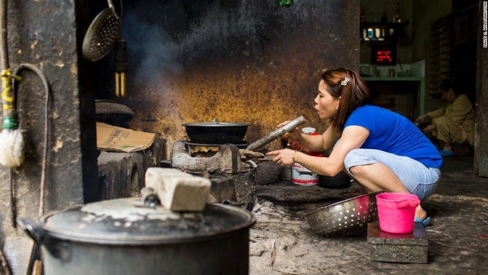 A woman at the restaurant blows on the coals to keep the flames going for a meal.
