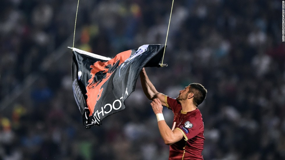 "Serbia's Stefan Mitrovic grabs the ""Greater Albania"" flag dangling from a drone that flew over Tuesday's European Championships qualifying match between Serbia and Albania. The incident at Belgrade's Partizan Stadium precipitated a brawl that forced the referee to abandon the match."