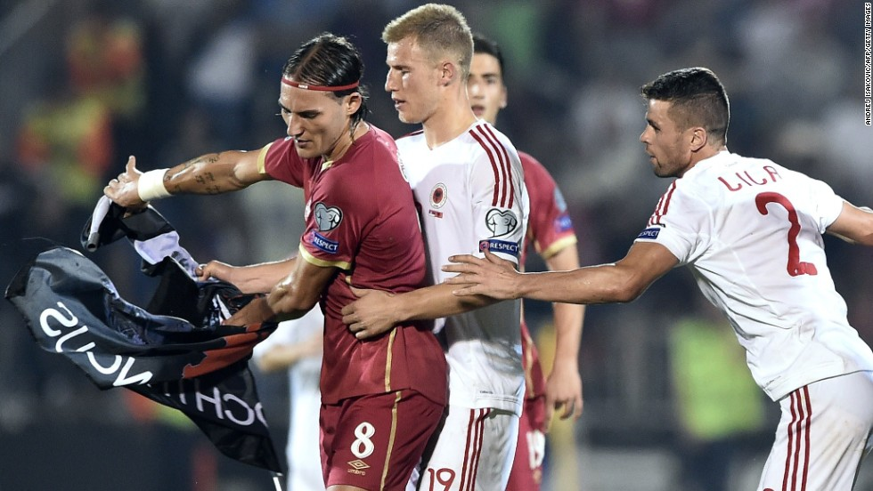 Serbia's Nemanja Gudelj, left, scuffles with Albania's Bekim Balaj, center, and Andi Lila, right, over the flag.