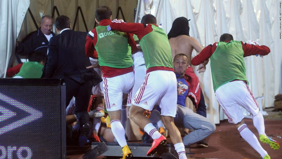 Albania's players make their way to the safety of the dressing room as fans take out their anger. Referee Martin Atkinson  took the players off the field 41 minutes into the goalless match.
