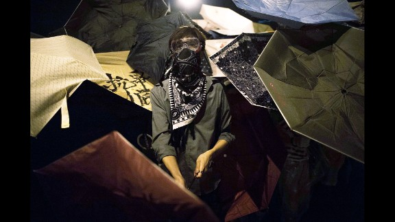 Pro-democracy protesters hide behind umbrellas to protect themselves from pepper spray on October 15.