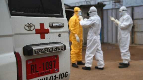 Caption:MONROVIA, LIBERIA - OCTOBER 13: Health workers dress in protective clothing before taking the body of an Ebola victim from the Island Clinic Ebola treatment center on October 13, 2014 in Monrovia, Liberia. A planned strike at Ebola treatment centers was averted as most nurses and health care workers reported for work, many saying they could not in good conscience leave their patients unattended. Health workers have been asking for increased hazard pay. They are one of the most high-risk groups of Ebola infection, as nearly 100 of them have died in Liberia alone. (Photo byCaption:MONROVIA, LIBERIA - OCTOBER 13: Health workers dress in protective clothing before taking the body of an Ebola victim from the Island Clinic Ebola treatment center on October 13, 2014 in Monrovia, Liberia. A planned strike at Ebola treatment centers was averted as most nurses and health care workers reported for work, many saying they could not in good conscience leave their patients unattended. Health workers have been asking for increased hazard pay. They are one of the most high-risk groups of Ebola infection, as nearly 100 of them have died in Liberia alone. (Photo by John Moore/Getty Images) )