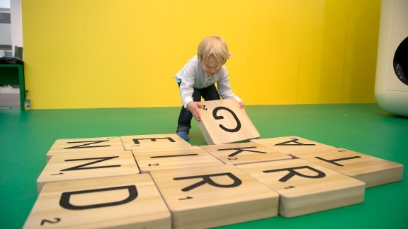 """Children play with a giant scrabble set as part of Carsten Holler's installation """"Gartenkinder"""", in which he the Gagosian Gallery's stand at Frieze was transformed into a children's playground."""
