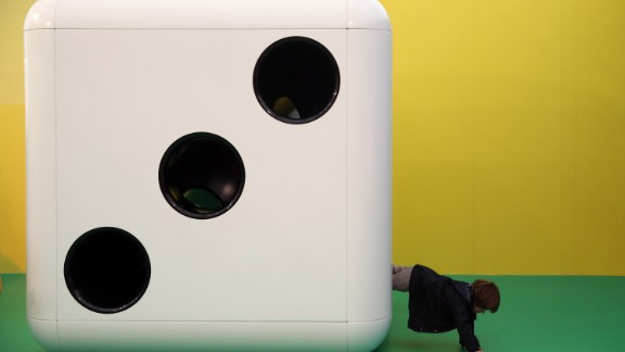 """It was the beginning of a week of the bold, the beautiful, and the downright bonkers. Here, a child climbs out of a huge dice, part of an installation by artist Carsten Holler titled """"Gartenkinder""""."""