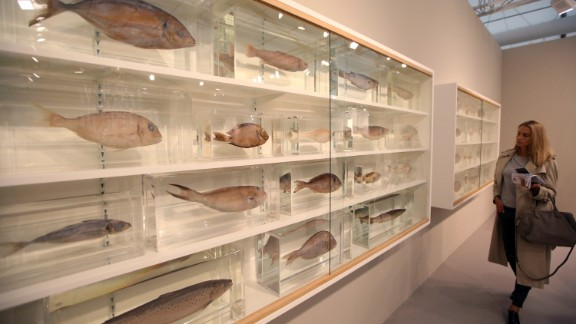 """The biggest names of the art world were represented, including Damien Hirst. His sculpture """"Because I Can't Have You I Want You"""" features many fish on shelves."""