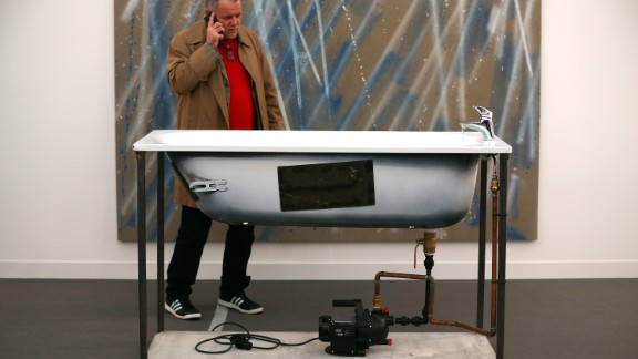 """A visitor inspects a disembodied bath, better known as a sculpture by Oscar Tuazon titled """"A Fountain""""."""