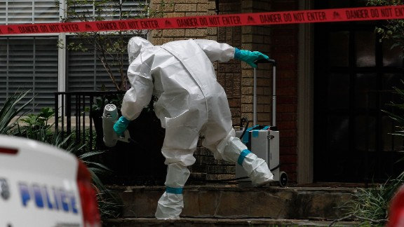 A man dressed in protective clothing treats the front porch of a Dallas apartment on October 12, 2014. The apartment is home to one of the two nurses who were diagnosed with Ebola after treating Thomas Eric Duncan, a Liberian national who traveled to Dallas and later died from the virus.