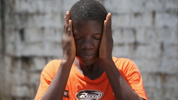 Ebola survivor Jeremra Cooper, 16, wipes his face from the heat while in the low-risk section of the Doctors Without Borders (MSF) Ebola treatment center in Paynesville, Liberia, on Thursday, October 16. The 8th grade student said he lost six family members to the Ebola epidemic before coming down sick with the disease himself and being sent to the MSF center, where he recovered after one month.
