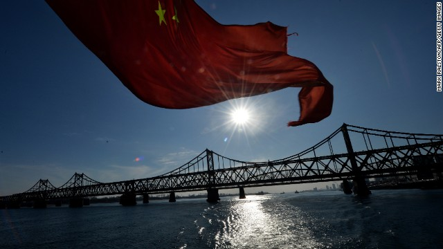 The Chinese flag flies from a boat beneath the Sino-Korean Friendship Bridge which leads to the North Korean town of Sinuiju from the Chinese border town of Dandong on December 16, 2013.