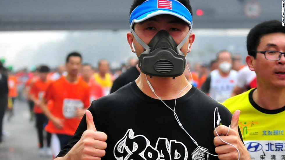 A competitor with a gas mask type mask gives the thumbs up as he competes in Sunday's 34th Beijing International Marathon.