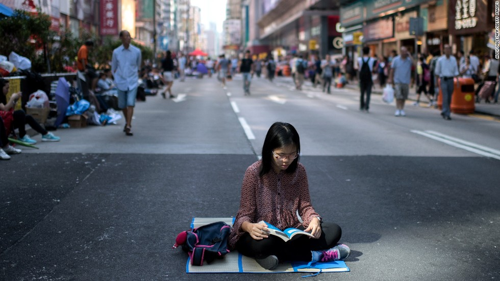 A woman reads on a road barricaded by pro-democracy protesters on October 19.
