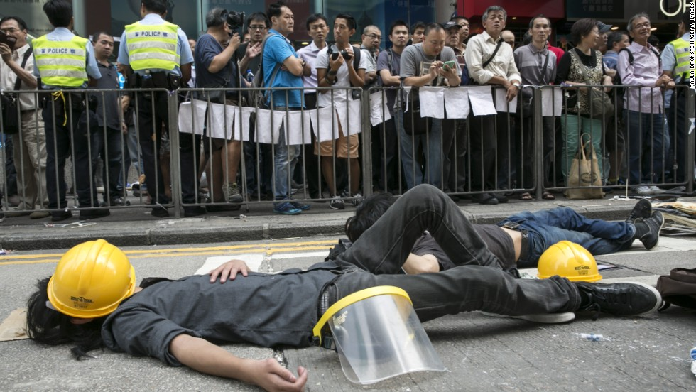 Pro-democracy protesters sleep next to a barricade on October 18 after reclaiming streets in Mong Kok after a night of violent scuffles with police.