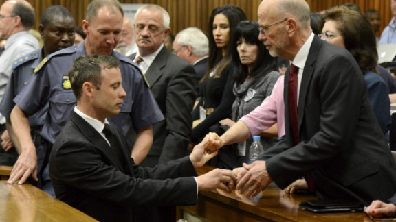 Oscar Pistorius reaches out to his uncle Arnold Pistorius and other family members as he is led out of court in Pretoria, South Africa, after being sentenced to five years in prison on Tuesday, October 21. Pistorius, the first double-amputee runner to compete in the Olympics, was sentenced for culpable homicide in the February 2013 death of his girlfriend, Reeva Steenkamp.