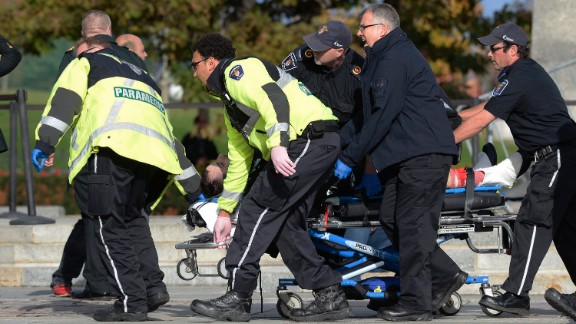 Paramedics and police pull a shooting victim away from the war memorial.